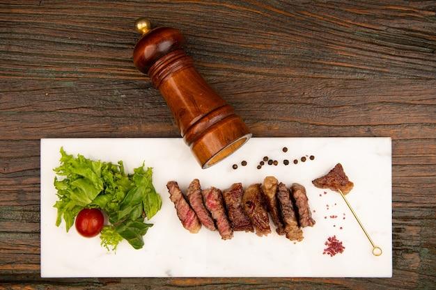La viande grillée est placée sur un plat en pierre noire à côté du couteau salière et poivrière