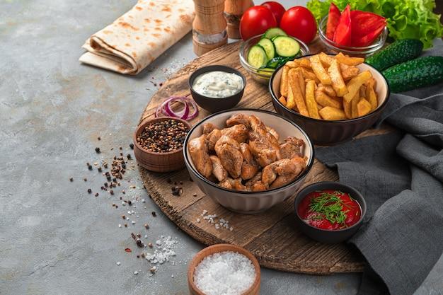 Viande grillée, frites et légumes sur un mur gris. déjeuner, ingrédients pour faire shawarma, burrito.