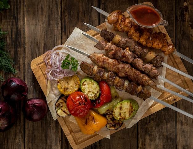 Viande grillée avec des légumes sur des brochettes sur des planches de bois, vue de dessus