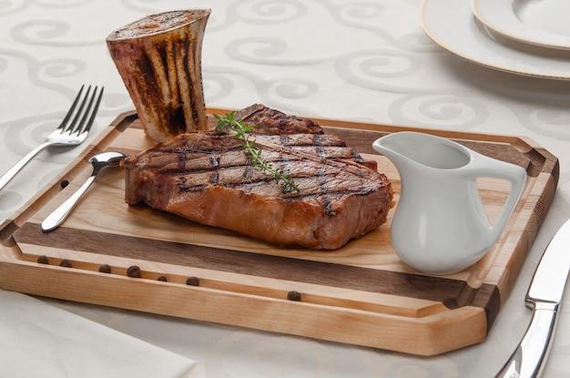 Viande grillée avec un os sur la planche avec la sauce et les couverts