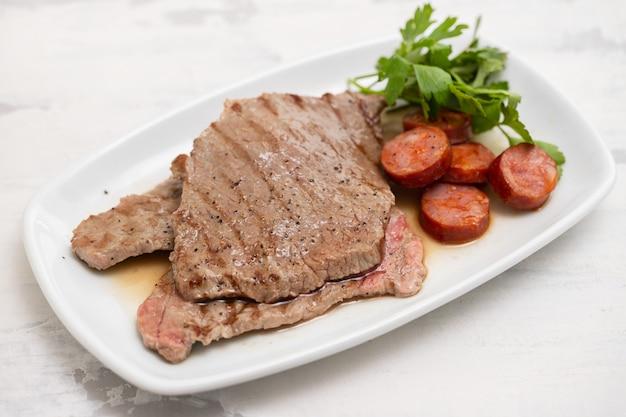 Viande grillée avec saucisse fumée sur plat blanc