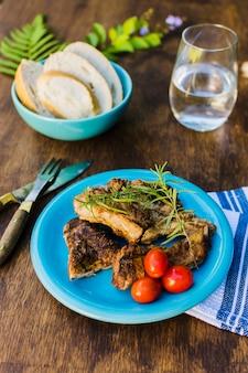 Viande grillée avec tomates cerises et pain