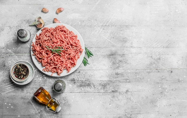 Viande hachée crue aux épices et herbes. sur un fond rustique.
