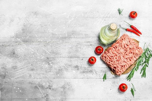 Viande hachée crue aux tomates, romarin et épices. sur fond rustique