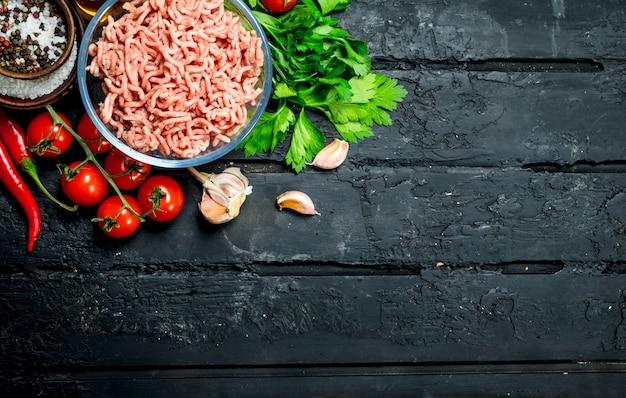 Viande hachée crue dans un bol avec des légumes et des herbes. sur fond rustique noir.