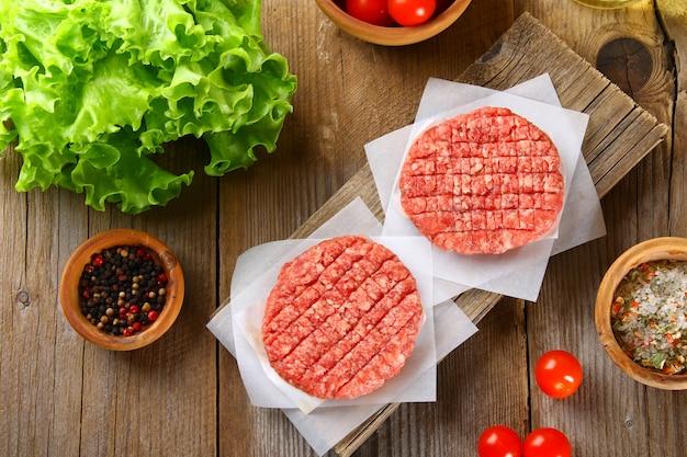 Viande hachée crue pour les hamburgers grillés faits maison cuisant avec des espaces et des herbes.