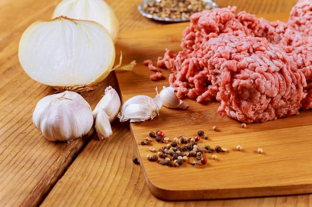 Viande hachée dans du papier de boucher avec oignon ail