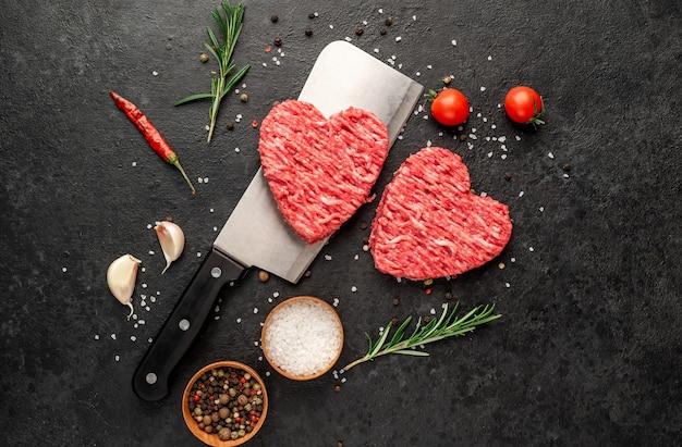Viande hachée en forme de coeur sur un couteau sur un fond de pierre