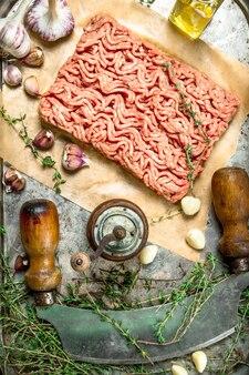 Viande hachée fraîche avec de l'ail et des herbes épicées sur le tableau noir