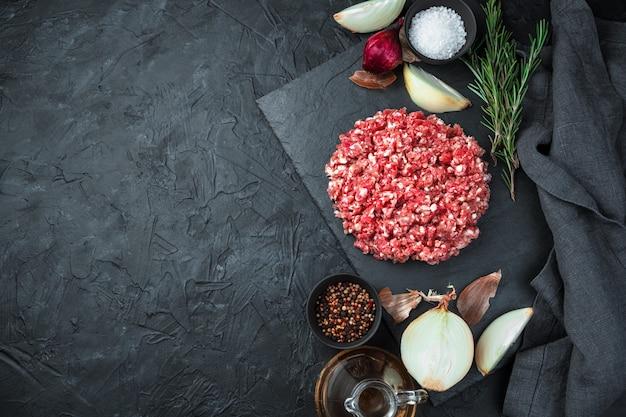 Viande hachée fraîche et juteuse au romarin, oignon, poivre et sel sur fond noir. vue de dessus, horizontale. concept de cuisine.