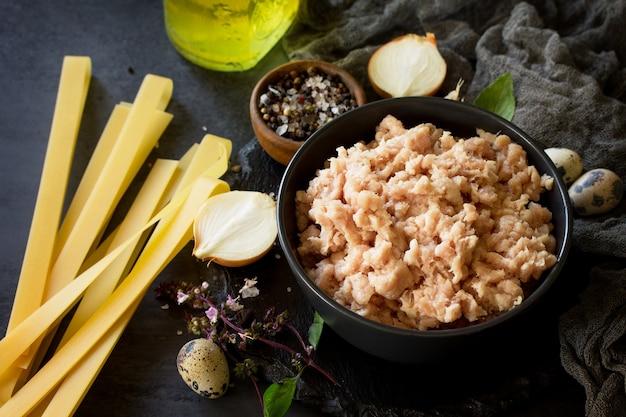 Viande hachée et ingrédients pour la cuisson de la viande hachée dans un bol sur une ardoise