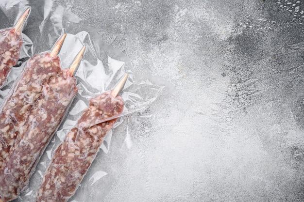 Viande hachée de mouton sur des brochettes dans un emballage sous vide, sur fond de table en pierre grise, vue de dessus à plat, avec espace de copie pour le texte