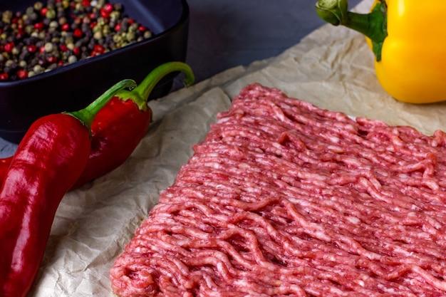 Viande hachée sur papier kraft posé sur une table lumineuse en bois piments rouges avec pe...