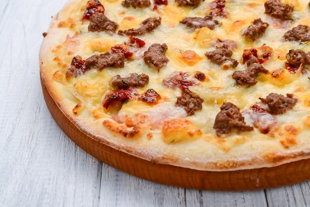 Viande hachée pizza tomate oignon rouge sur une surface en bois