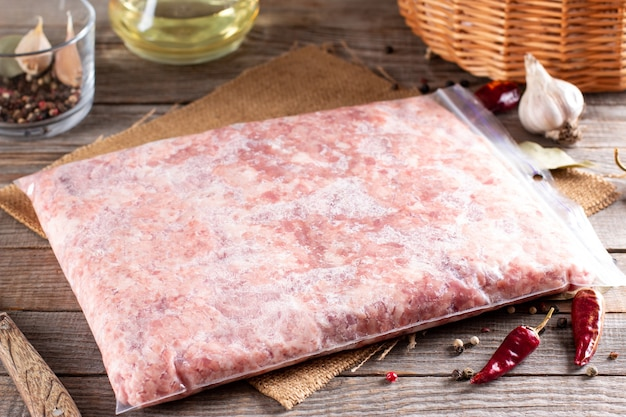 Viande hachée de porc congelée sur une table en bois. des surgelés
