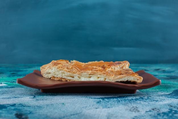 Viande hachée savoureuse en pâtisserie salée à bord, sur la table en marbre.