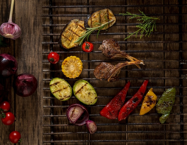 Viande et légumes grillés sur un treillis métallique, vue de dessus. fond en bois