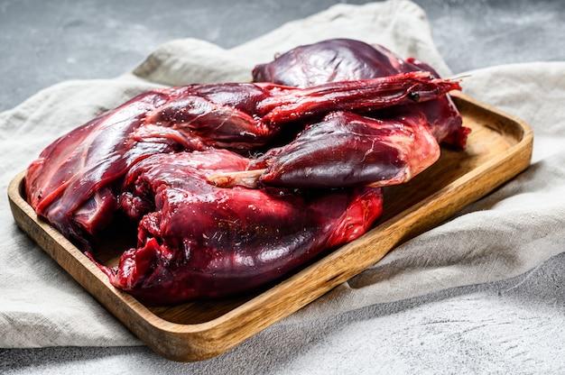 Viande de lièvre. lièvre sauvage frais sur une table en bois avec des légumes et des épices.