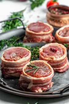Viande marbrée fraîche et crue steak filet mignon. steaks médaillon enveloppés de bacon servis sur un vieux plateau en métal. image verticale.