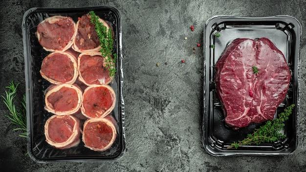 Viande marbrée fraîche et crue steak filet mignon. steaks médaillons enveloppés de bacon sur fond de béton foncé. produits à base de viande emballés.