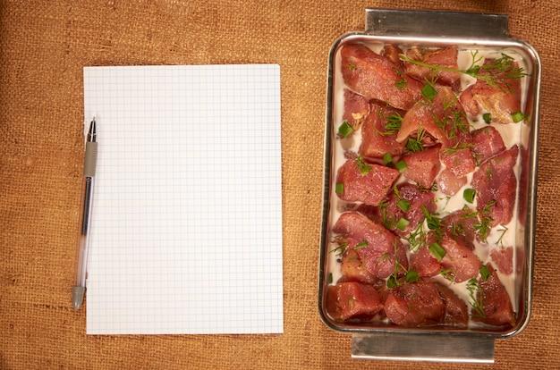 Viande marinée au lait et aux légumes verts dans un plat profond en acier recouvert d'un linge propre avec une feuille de papier vierge et un stylo à bille