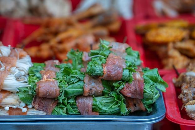 Viande marinée aux herbes sur le comptoir d'un restaurant de rue pour griller dans le village de montagne de sapa, au nord du vietnam, en gros plan. cuisine asiatique traditionnelle pour touriste