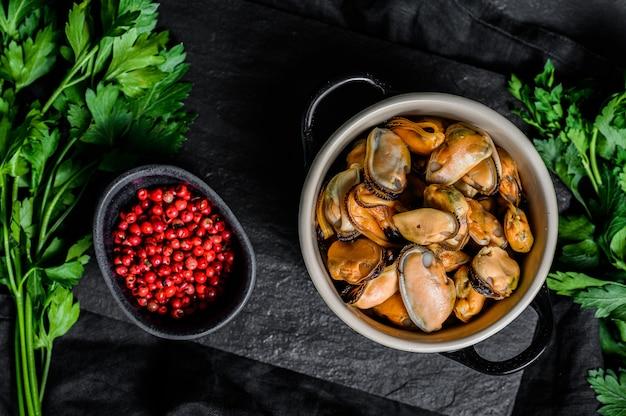 Viande de moule crue sur une planche à découper avec du persil. fruits de mer sains.