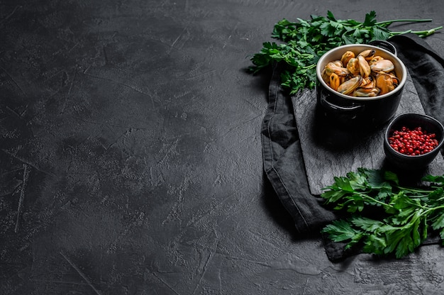 Viande de moule cuite sur une planche à découper avec du persil. fruits de mer sains.
