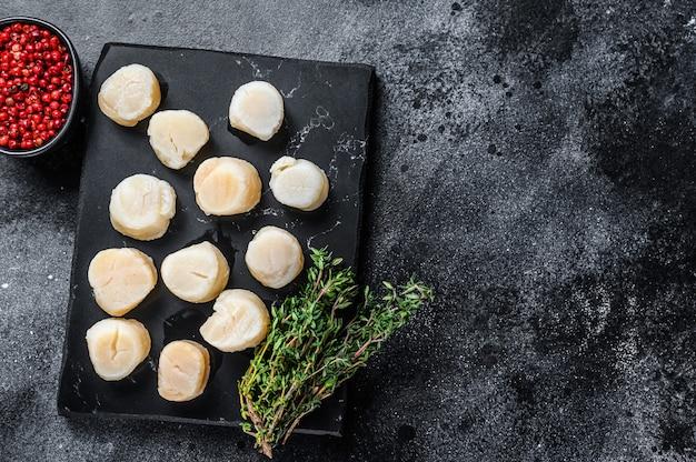 Viande de pétoncles frais de fruits de mer sur une planche de marbre.