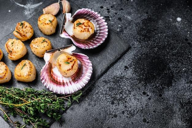 Viande de pétoncles frits aux fruits de mer avec du beurre dans une coquille