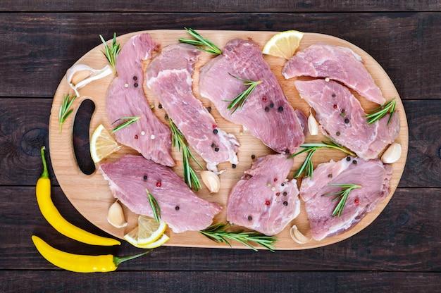 Viande plate crue pour steak (côtelette) avec des épices sur une planche à découper sur une table en bois foncé. vue de dessus.