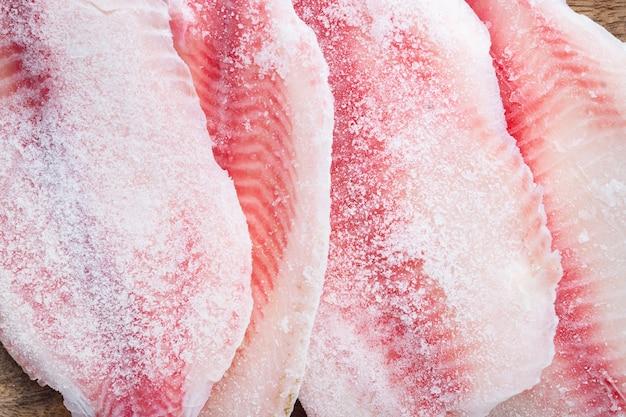 Viande de poisson tilapia cru congelé, sur table blanche, vue du dessus