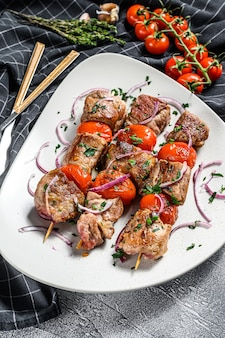 Viande de porc et de bœuf barbecue sur des brochettes en bois. fond gris. vue de dessus.