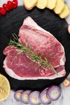 Viande de porc crue sur une assiette en ardoise noire avec un ingrédient d'épice - romarin, gingembre, piment, oignon.