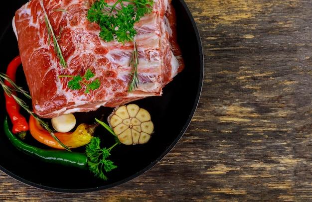 Viande de porc crue sur des côtes et des herbes.