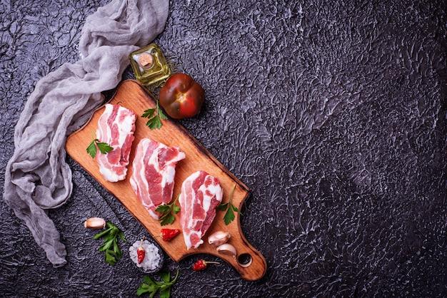 Viande de porc crue et ingrédients pour la cuisine. vue de dessus