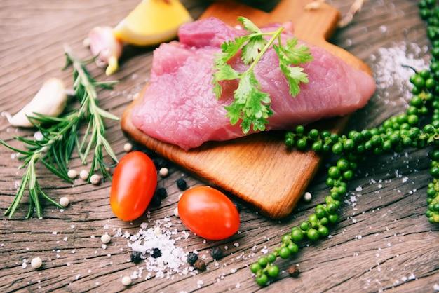 Viande de porc crue sur une planche à découper en bois sur la table de la cuisine pour la cuisson du steak de porc rôti ou grillé avec des ingrédients aux herbes et aux épices porc frais