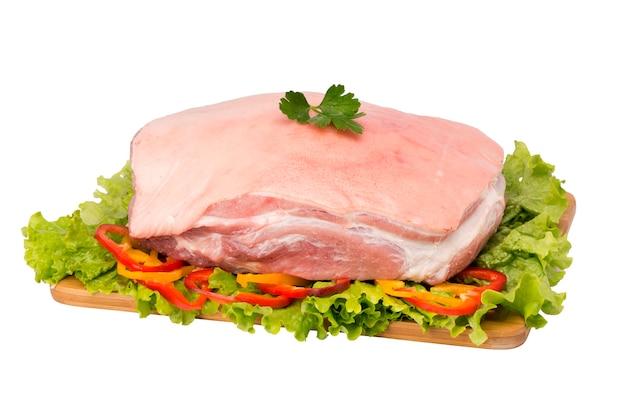 Viande de porc crue sur une planche à découper sur fond blanc.