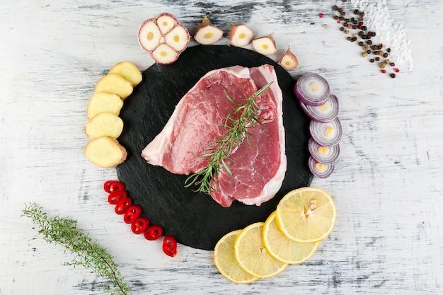 Viande de porc crue sur une plaque d'ardoise noire avec un ingrédient d'épice