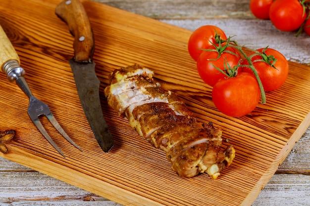 Viande de porc cuit sur planche à découper tomate, sur fond, vue haut, gros plan