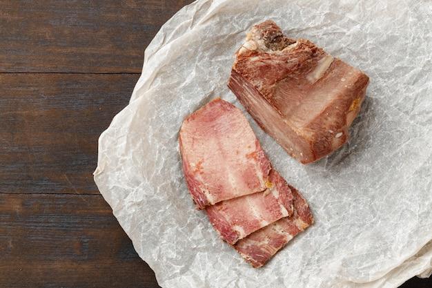 Viande de porc cuite en tranches sur fond de bois