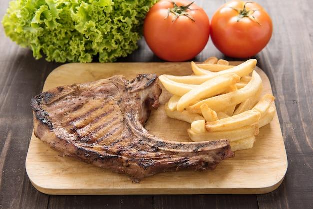 Viande de porc grillée avec frites et légumes sur fond de bois.