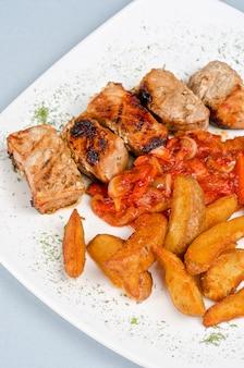 Viande de porc kebab grillée avec pomme de terre rôtie et légumes