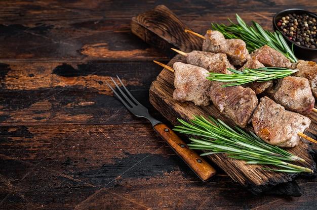 Viande de porc shish kebab sur des brochettes aux herbes sur une planche de bois. table en bois sombre. vue de dessus. copiez l'espace.