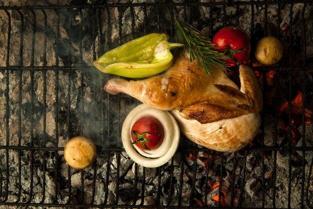 Viande de poulet aux légumes sur une grille métallique posée sur du charbon de bois le plat est cuit et fumé sur du charbon de bois