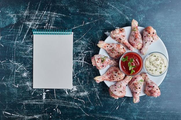 Viande de poulet crue dans une assiette blanche avec un livre de cuisine de côté.