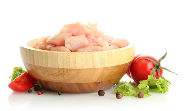 Viande de poulet crue dans un bol en bois, isolé sur une surface blanche