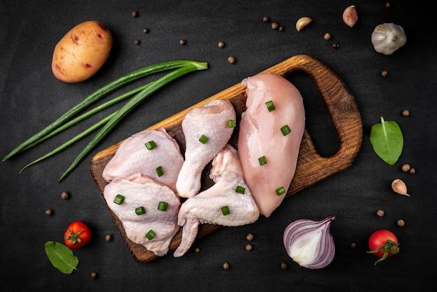 Viande de poulet crue sur fond noir.