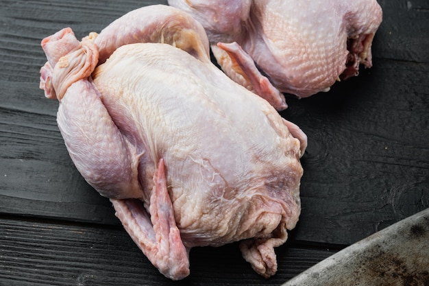 Viande de poulet entière non cuite biologique crue, sur une table en bois noire