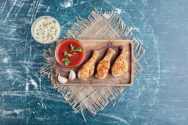 Viande de poulet épicée sur une planche de bois avec des sauces.